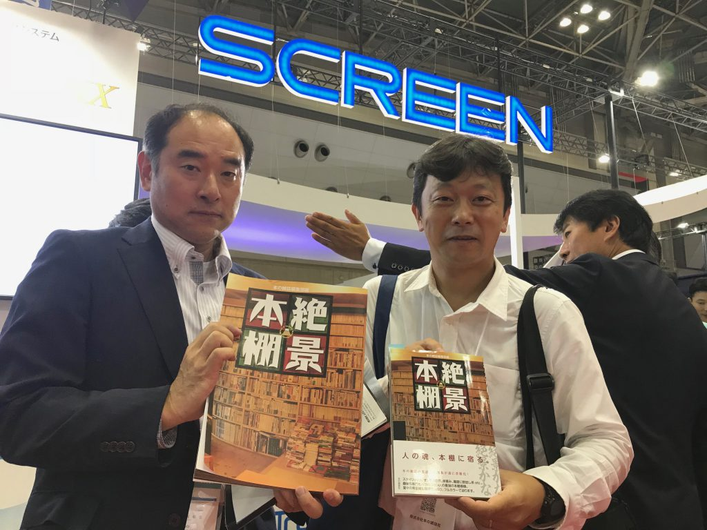 拡大版『絶景本棚』を持つメディアテクノロジージャパンの山岡さん(左)と、本の雑誌社の杉江さん。