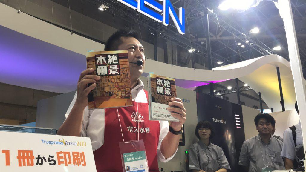 SCREEN社のブースで『絶景本棚』の紹介をする実演販売士のボス水野さん。両手の本のサイズの違いに注目!